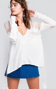 Fall in love with our Prima Sweater. This garment is incredibly detailed with engineered rib and baby ruffle that falls along the sleeves, as well as a center front and back rib detail. Features contrasting sizes of pointelle hole details along the bodice and the bicep. Bottom of bodice has an adjustable opening complete with draw cords with tassel ends and side slits.  In Multi.  53% Cotton, 36% Modal  Model wears a size small