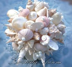 This bouquet is named Hinewai. Hinewai is a simple bouquet of shells, ribbon and pearl accent. Hinewai is also an instant wedding heirloom, to be enjoyed for years to come!  This is a variation of the original with slight blush tones.Delicately handwired shells and accents presented in this crafted bouquet. A multitude of real shells are coordinated with pearl accents. The bouquet is simply natural shell white.   Sea Urchins and Sand Dollars are prominent and unique to this design.Hinewai...