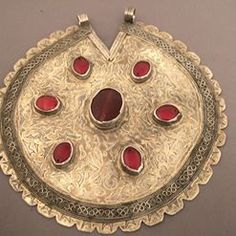 """Silver gilded with fire, carnelians, glass paste, Turkmenistan   Description ::  An old pendant """"tekke"""" from Turkmenistan in silver and gilded with fire: a central bead of carnelian and 6 red glass paste beads ... The pendant dates from the first half of the 20th century : a wonderful piece for collectors and also easy wearable by all women!  Weight:152,4gr  Diameter:6,02 inch  Still for sale in my Gallery at 28, Galerie du Roi at 1000 Brussels and also on my website www.halter-ethnic.com"""