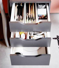 Nahaufnahme von IKEA ALEX Schubladenelement in Grau. In den geöffneten Schubladen sind Arbeitsutensilien zu sehen.