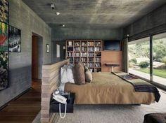No centro do quarto, o painel de madeira serve de cabeceira para a cama que, de frente para a área externa, complementa o estilo industrial e rústico do espaço.