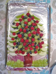 "Fruit salad arranged in Christmas tree shape. Arrange fruit dip on the bottom for ""snow"""