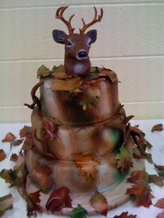 "Deer Hunter / Camo Groom's Cake - Groom received a similar picture of this cake through email and decided this was what he wanted for his cake.  8"", 10"", and 12"" round tiers were covered in fondant and airbrushed for camo look.  Deer head was store purchased.  Leaves are gumpaste and airbrushed.  This cake was  a lot of fun to make.  Thanks for looking."