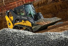 Right hand view of a  John Deere 317G Compact Track Loader transporting gravel at a construction site