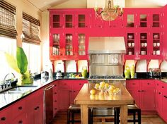 like the red cabinets with the black counter tops, neutral walls, and the wood tones