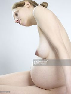 Stockfoto : Side view of naked pregnant woman sitting