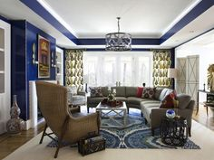 High-gloss, bright blue walls lend instant sophistication to this eclectic, pattern-filled living room. (Design by Lorna Gross of Savant Interiors and photography by Angie Seckinger)