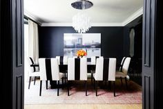 We adore the sexy drama of the dining room design in Molly Sims' Los Angeles home, especially since the dark painted walls and a striking chandelier are balanced by layered rugs and graphic upholstery.