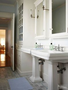 The master bathroom is one of the few rooms that needed new flooring; new gray-blue marble tiles anchor the all-white room. Charming sconces, glass-front cabinet doors, and vintage-style pedestal sinks complete the cottage-style look.