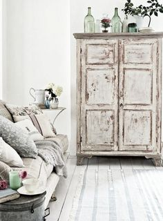 This white  distressed cabinet Adds texture and interest to an all white room. Love it!