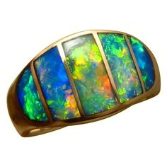 An Opal ring with Opal as good as it gets!  A 14k Gold very wide band is inlaid with five very bright and colorful Opals.