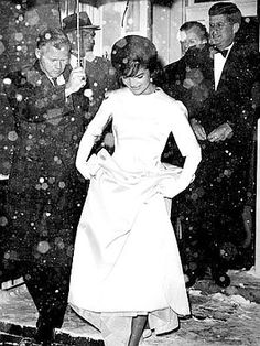 1961: Jackie Kennedy stepping out into the snowfall en route to Inaugural Gala with JFK behind her.