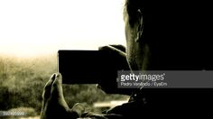 Foto de stock : Cropped Image Of Man Photographing From Mobile Phone Against Window