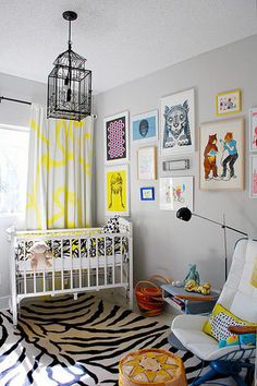 gender neutral nursery design with gray walls paint color, white crib, white black zebra rug, eclectic art gallery, iron lantern chandelier and gray yellow window panels curtains.