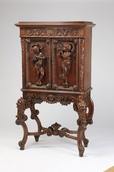 "Italian Renaissance Revival figural cabinet on stand, 19th century, the rectangular top surmounting a relief carved entablature above two paneled doors carved in relief with figures of putti playing music with acanthus leaf borders, the shaped apron carved with a figural mask of a winged bust flanked by flowers, the whole resting on four C-scroll legs carved with figural masks of Bacchus with a conjoined ""X"" stretcher and central finial."