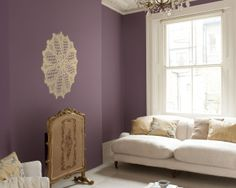 """Osez le romantisme avec un violet charbonneux. Ici, le violet mat s'associe aux teintes naturelles pour créer un salon très """"boudoir"""", auquel la grande applique en dentelle ajoute une touche de modernité."""