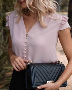 Pretty pink blouse with chic black handbag.