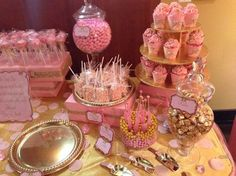 Platters and cupcake holder? Glass jars filled with pink and gold covered candies. Pink boxes adorned with gold ribbon for setting food at different levels.