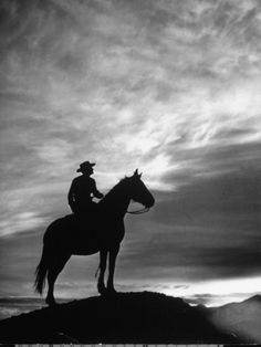 Silhouettes of Cowboy Mounted on Horse Premium Photographic Print by Allan Grant at Art.com