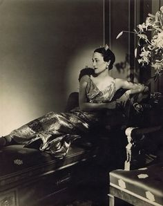 Wallis Simpson (before becoming the Duchess of Windsor) photographed in 1935 reclining on a chaise lounge among exotic lilies.  Her lame dress was by Mainbocher.  In her hair, ruby and diamond clips.  On her left wrist, the tell-tale jeweled crosses from the Duke of Windsor with their private messages.  Photo by Horst P. Horst.