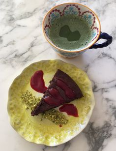 Wheat free chocolate cake with raspberry coulis and pistachio crumb. Served with Macha green tea.