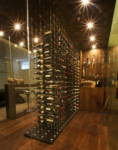 Back-to-back bottles in glass enclosed custom wine cellar featuring Cable Wine System.