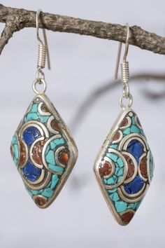 Bring exotic energy to your bohemian style with the bold tribal design of these awesomely eclectic Afghani diamond mosaic earrings.  Turquoise, coral, and indigo resins dance together in a unique mosaic of color, set amid stunning crescent slivers of shimmering white metal.