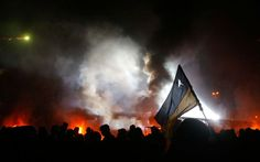A Ukrainian flag is illuminated by the small space of clear sky as Ukrainian protesters trudge on in the background.