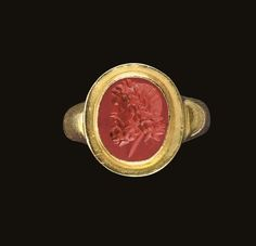 A ROMAN RED JASPER RING STONE  Circa 1st Century B.C.-1st Century A.D.  The flat oval stone engraved with a profile bearded head of Jupiter, a laurel wreath in his curly hair; mounted as a ring in a modern gold setting ½ in. (1.3 cm.) long; ring size 7¾