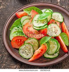 Tomato and cucumber salad with black pepper and basil - stock photo