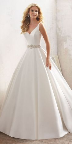 Understated and Elegant, This Stunning Marcella Satin A-Line Bridal Gown Features a Crystal Beaded Sheer Back and Waistline. Covered Buttons Trim the Back and Train.