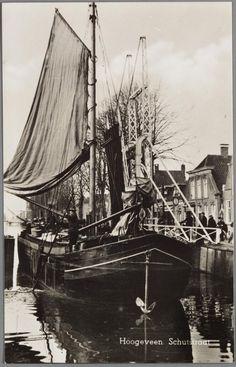 Een lege Hasselteraak wordt door de geopende brug gezeild en tevens geboomd om het schip door de brug te krijgen. Het stokanker hangt voor de boeg.