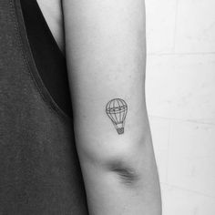 Fine line air balloon tattoo on the back of the right arm.