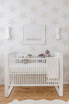 White nursery with star wallpaper.