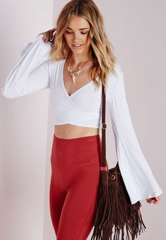 Work some major festival vibes this season in this white crop top. With figure flattering wrap over feature to the top and on trend bell sleeves this top is a total dreamboat. Team with high waisted faux suede shorts and lace up gladiator s...