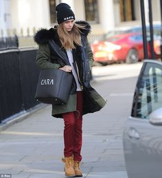 On top of the trend: Cara Delevingne was dressed in a trendy and casual parka jacket, NSFW beanie hat, red jeans and Timberland boots