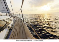 Yacht sailing towards the sunset - stock photo