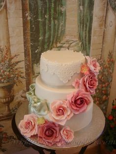 Wedding cake with roses, silver ribbon and lace