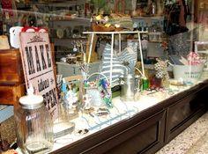 Escaparate de la semana en VYP Regalos, Palma, con complementos y detalles originales para la casa. Bolso de playa, mesita blanca, cuadro madera...