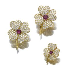 Gold, diamond and ruby four leaf clover brooches by Van Cleef & Arpels.
