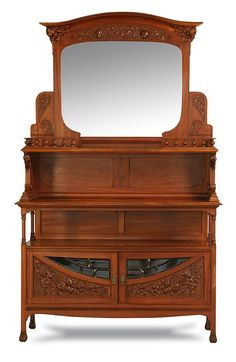 "19th century French Art Nouveau walnut buffet, with flared crest supported by carved pomegranates, over a central beveled mirror with display gallery surmounting two open display shelves, over a base cabinet with leaded and beveled glass inserts on the lower doors also with relief carved branches of pomegranates, 94""h x 58""w x 21""d."