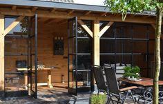 Stalen taatsdeuren met glas in eiken veranda.  Een taatsdeur is een deur die om zijn verticale as draait, waarbij de as zich niet op één van beide stijlen bevindt. De draaipunten bevinden zich aan de boven- en onderkant van de deur. Het voordeel van een taatsdeur is dat er geen kozijn nodig is om de deur aan af te hangen. Kijk voor meer foto's op de website van Bouwbedrijf HaBé.