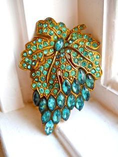 Offering an Art Nouveau dress/fur clip with teal paste stones in a grape cluster…