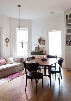 Farah's living/dining room in Brooklyn on Design Sponge. Like the simple white walls and uncluttered space.