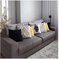 Sofá cinza e almofadas com contraste.