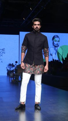 A simple plain black half-sleeves jacket paired with a black floral printed kurta go well with each other. Also, the white pyjama gives a perfect contrast to the kurta. Wedding Kurta For Men, Wedding Dresses Men Indian, Wedding Outfits For Groom, Wedding Dress Men, Wedding Men, Wedding Suits, Wedding Attire, Mens Indian Wear, Mens Ethnic Wear