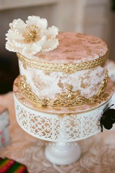 a vintage inspired bridal luncheon cake. Blush pink with antique gold accents and a white sugar flower topper