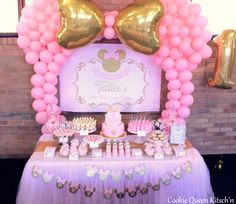 Minnie Mouse Pink Gold Dessert Buffet Table. Personalised Backdrop featured with matching printables and chocolate bars, candy bars. Desserts featured are Custom Minnie Cookies, Cupcakes, Oreo Bites, Strawberry Mousse Pots and Lemon Cheesecake Pots, our great Minnie Ears Cakepops. Sydney based.