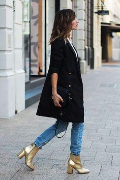 Duo de calça jeans com casaco alongado preto e bota metalizada dourada.