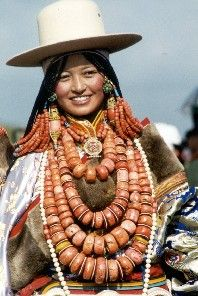 A Tibetan woman in her fabulous traditional attire - coral or amber and white magnecite.
